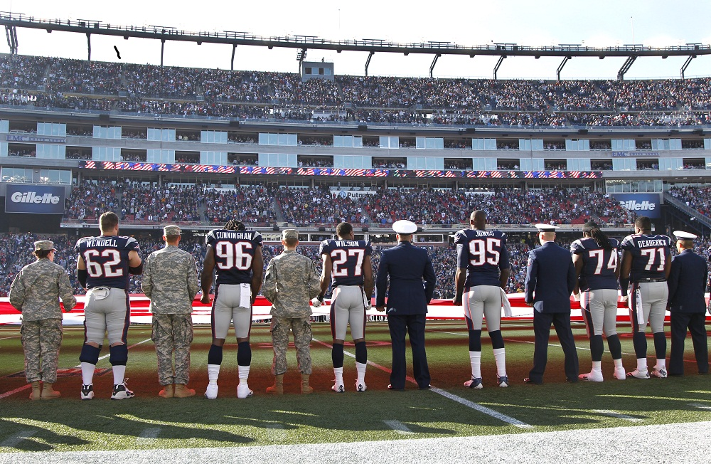 New England Patriots players line up with service members for the national anthem prior to an NFL football game against the Buffalo Bills at Gillette Stadium in Foxborough, Mass. Sunday, Nov. 11, 2012. The military was honored with the Salute to Service program as part of the Veterans Day weekend. (AP Photo/Elise Amendola)